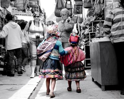 Sisters walk together in a market Sunday in Pisaq